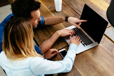 Closeup of couple using laptop at cafe
