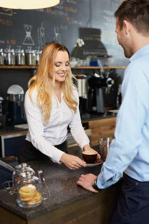 Jolie barista donnant savoureux cappuccino au client au café Banque d'images - 96002729