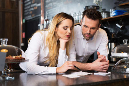 Two cafe managers counting revenue