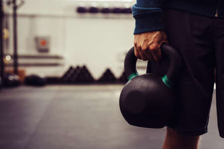 Close-up of man holding heavy kettlebell at gym