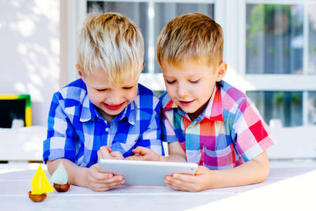 Two brothers having fun playing on digital tablet outside the home Imagens