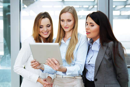 Group of three businesswomen looking at a digital tablet held by one of them 写真素材