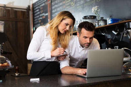 Two restaurant owners working with laptop