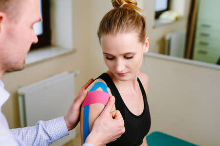 Physical therapist applying kinesiotaping on injured shoulder of young woman