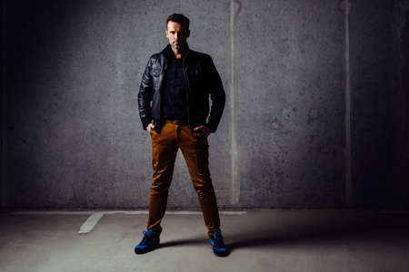 Serious man in leather jacket looking at camera, standing in empty garage against concrete wall Standard-Bild