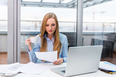 Young female business owner busy working at desk in office