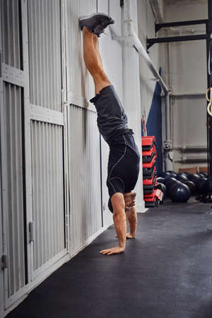 Bodyweight exercise, man standing on hands at gym