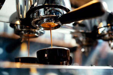 Close-up of espresso pouring from coffee machine. Professional coffee brewing Standard-Bild