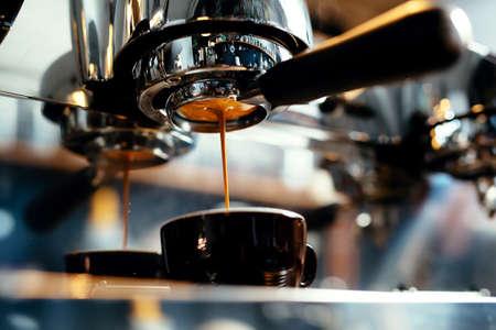 Primo piano di caffè espresso che versa dalla macchina del caffè. Preparazione professionale del caffè