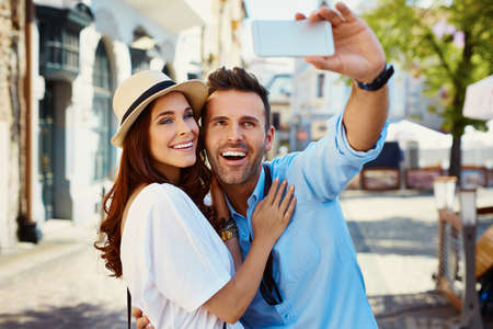 Happy couple taking selfie on the city street