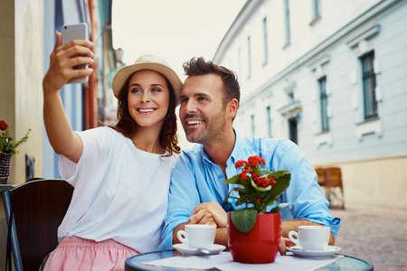 Happy couple taking selfie in outdoor cafe