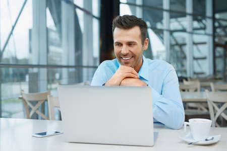 Handsome businessman at modern office working with laptop Foto de archivo
