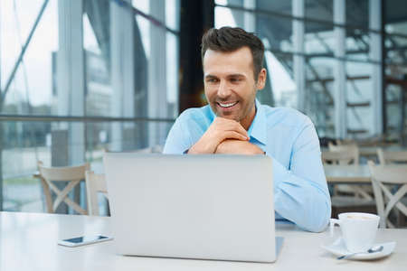 Handsome businessman at modern office working with laptop Standard-Bild