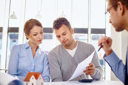Young couple reading loan contract for new home