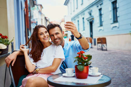 Couple on vacation taking selfie in outdoors cafe