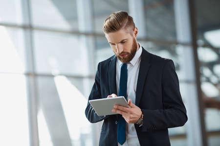 Modern hipster businessman working on digital tablet at office Foto de archivo