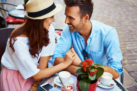 Couple in love sitting in cafe looking at each other