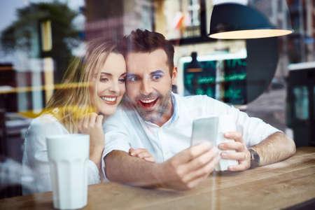 Couple taking selfie in coffee shop