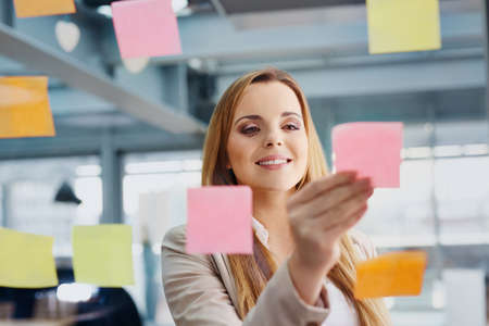 Happy designer sticking notes on window at office