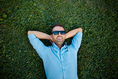 attractive man with sunglasses relaxing on the grass with his hands under the head