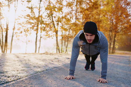 young man doing push ups exercise in park during fall Reklamní fotografie