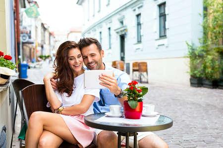 Tourist with digital tablet in street cafe Foto de archivo