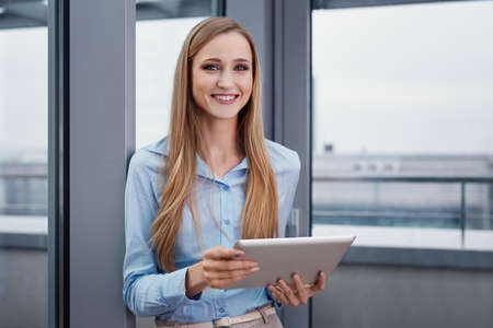 Cheerful woman at office standing with digital tablet