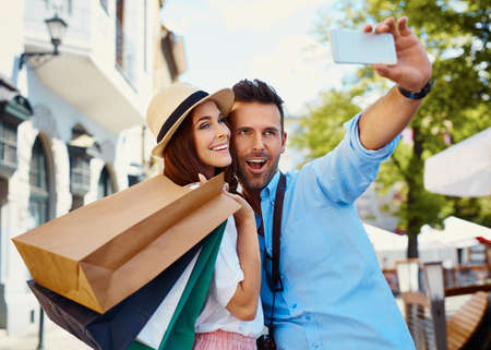 Happy couple taking selfie after shopping in the city Foto de archivo