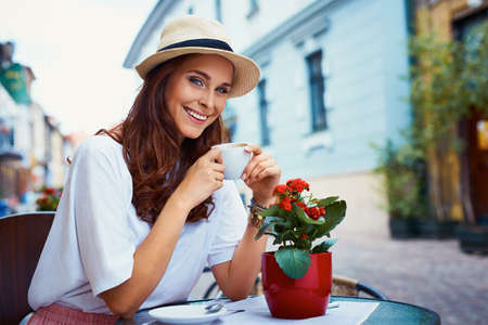 Attractive woman drinking coffee in outdoor cafe