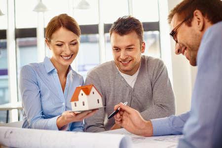 Happy couple choosing new home design with architect Foto de archivo