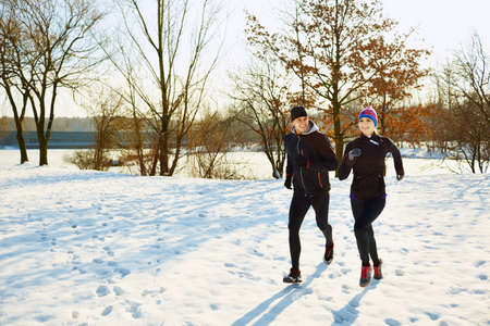 Caucasian couple running at winter