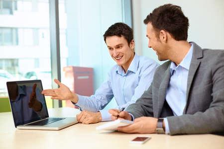 Two businessmen working on laptop in modern office Foto de archivo