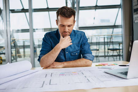 Thoughtful male architect working at office