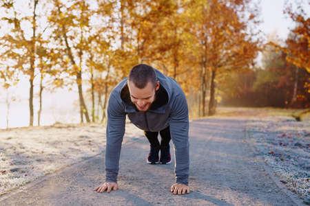 Happy man doing push ups exercise during morning running workout