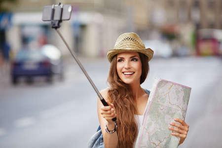 Happy tourist taking selfie with stick, holding map, visiting city Foto de archivo