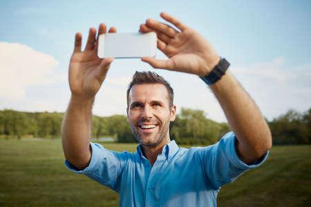 Happy mid adult man taking selfie in park Foto de archivo