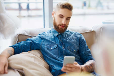 Hipster with tatoos texting on smart phone, sitting on couch in cafe