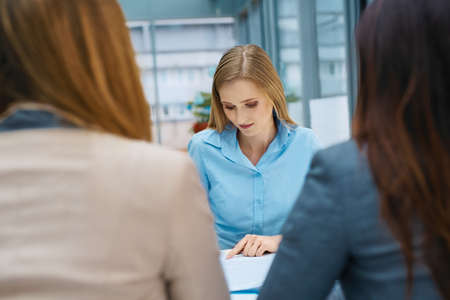 Young woman signing contract after job interview at modern office