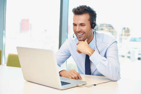 Happy businessman with laptop and headset talking during video conference Foto de archivo
