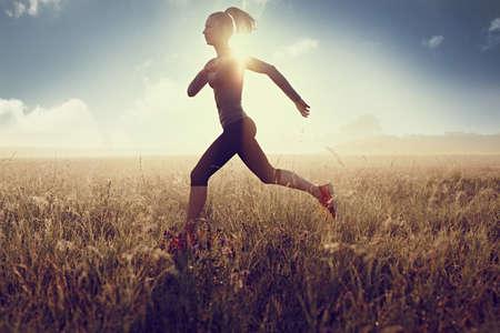 Slim woman running at morning on filed during sunset