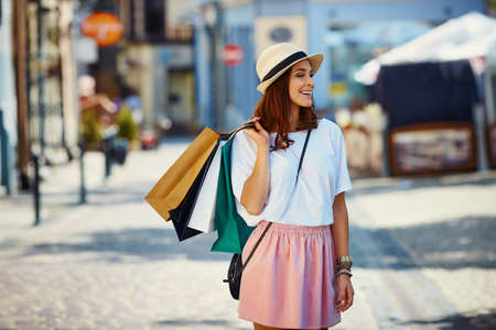 Happy young woman shopping, standing with bags on the city street Foto de archivo