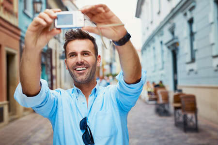 Handsome young man taking selfie with camera  on vacation