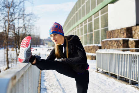 Female runner stretching before running at winter Banque d'images
