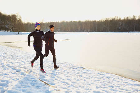 Young couple running during winter