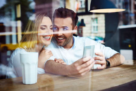 Happy couple at coffee shop using smartphone