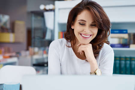 Happy store manager working on laptop