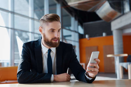 Stylish hipster with suit browsing his smartphone at modern office
