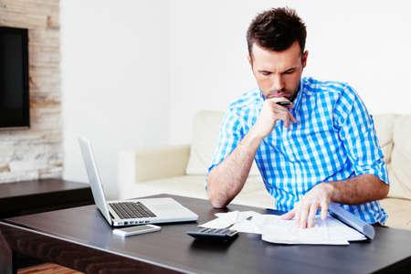 Young man paying bills at home