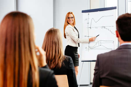 Photo of a female professional drawing a graph during a training
