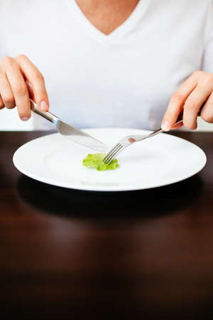 Man on diet cutting a tiny piece of lettuce on a white plate